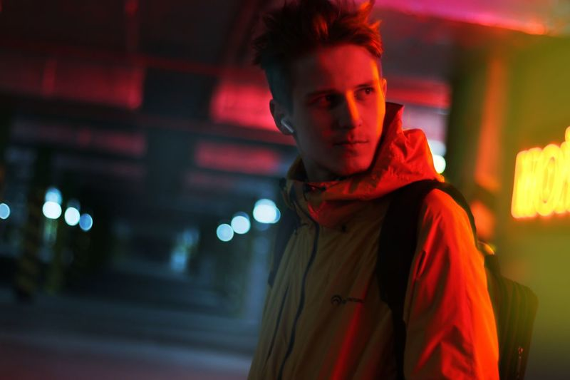 Парень на парковке Night Illuminated One Person Young Adult Young Men Portrait Lifestyles Looking Architecture Clothing Focus On Foreground Adult Leisure Activity Standing City Nightlife Men Side View Red Warm Clothing