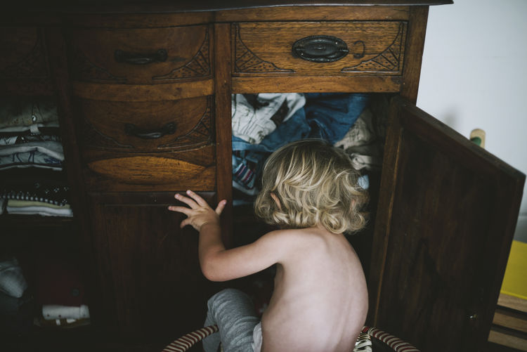 Rear view of boy sitting by cabinet