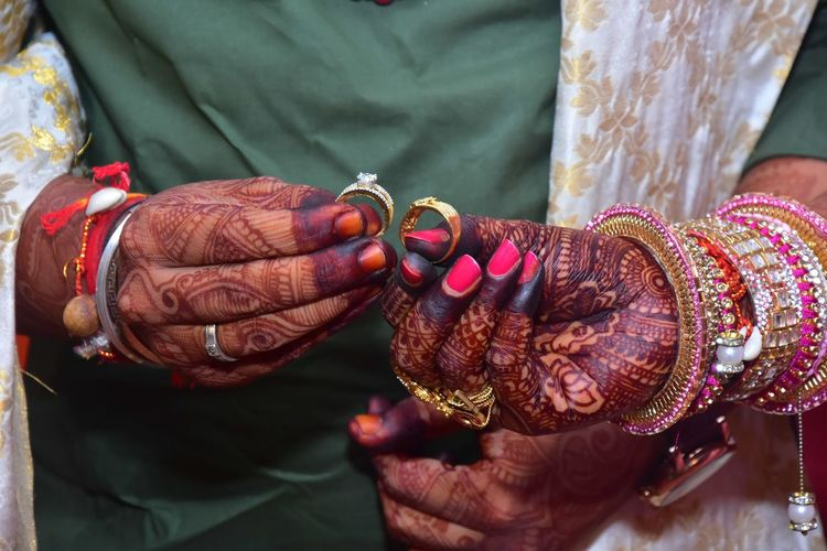 Midsection of couple holding rings in wedding ceremony