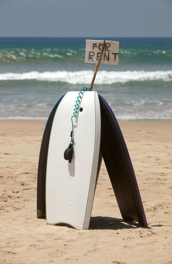 Body board on sand at beach against sea