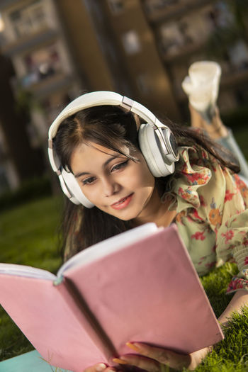 Portrait of young woman reading book