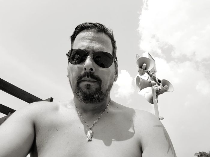 Portrait of shirtless man wearing sunglasses against megaphones and sky