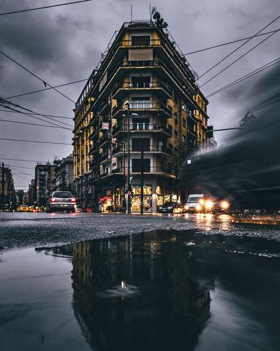 Illuminated buildings by street against sky at dusk