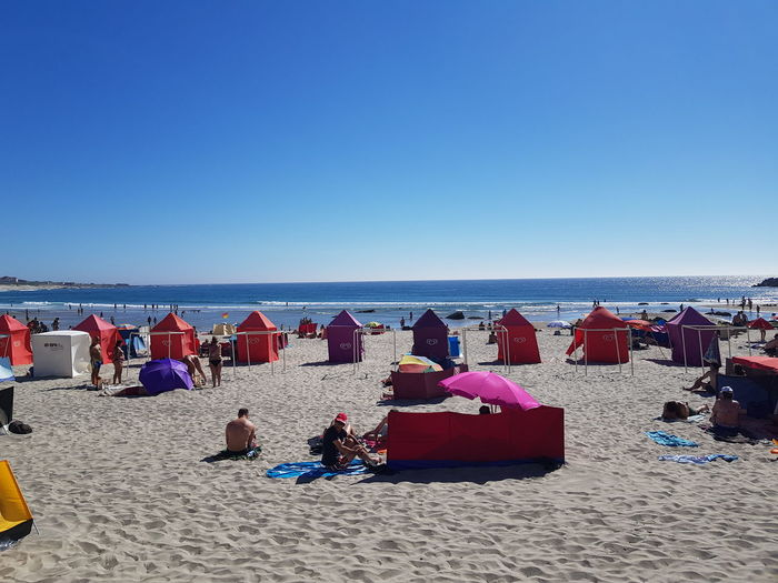 People relaxing on beach against clear sky