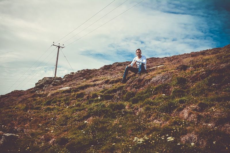 Low angle view of man sitting on mountain against cloudy sky