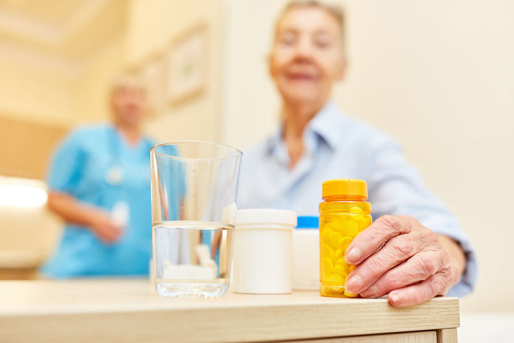 Woman holding bottle on table with nurse in background