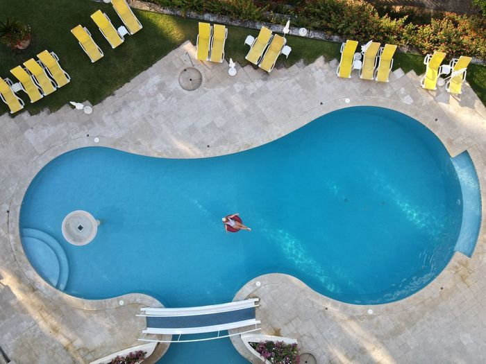 Aerial view of woman sitting on poo raft in swimming pool