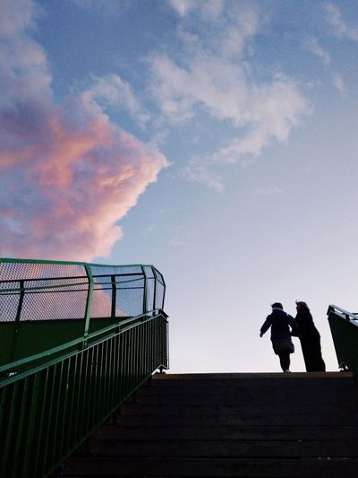 Low angle view of silhouette people standing on railing against sky