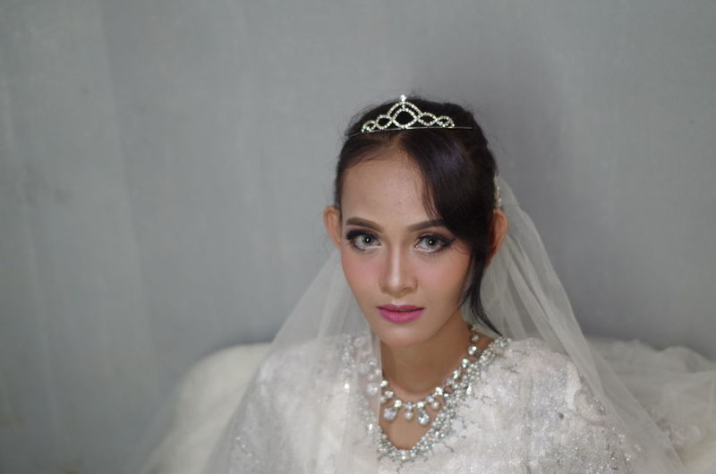 Portrait of bride sitting against wall
