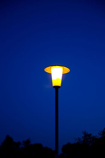 Retrostyle Blue Clear Sky Copyspace Dark Blue Darkness And Light Illuminated Lighting Equipment Low Angle View Night No People Old Streetlight Only One Outdoors Sky Street Light Tree Yellow Yellow Color