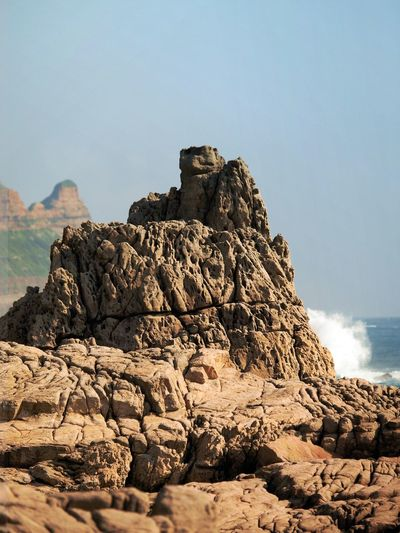 The effects of erosion can be seen on the rocks of 'Dragon's Cave Bay' (Longdongwan), north-east Taiwan. Cape Bitou, to the north-west, can be seen in the left of the picture. Cape Bitou Dragon's Cave Gongliao District Longdongwan Rock Formation Ruifang District Taiwan Beauty In Nature Clear Sky Day Erosion Nature No People Outdoors Rock - Object Rock Formation Scenics Sky Tranquility Travel Destinations