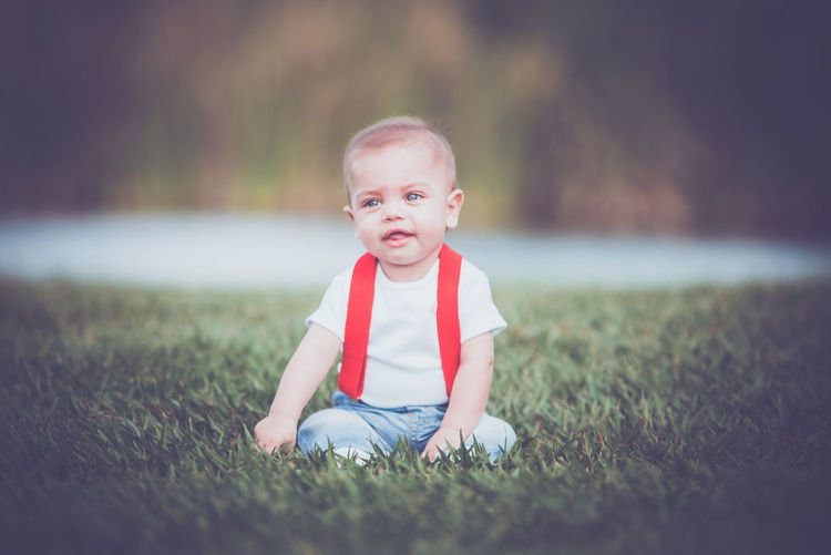 Portrait of cute girl sitting on field