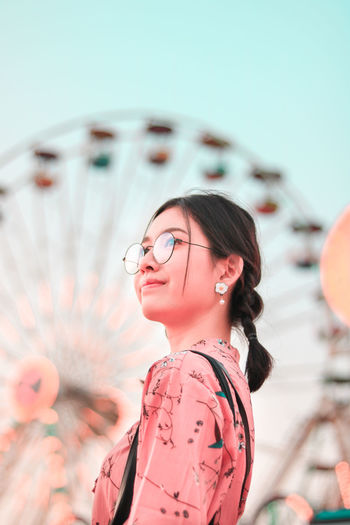 Portrait of young woman with carousel standing in amusement park