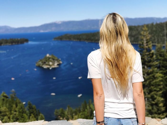 Rear view of woman with long blond hair standing against sea