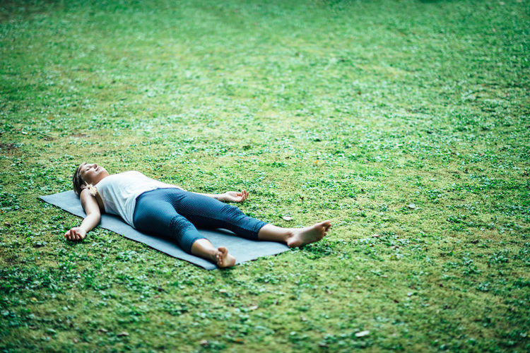 Young woman practicing shavasana in park
