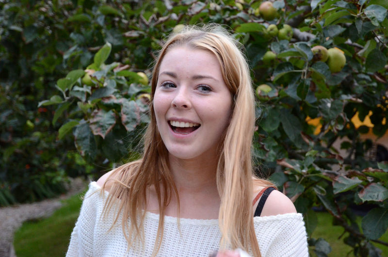 Happy young woman standing against apple tree