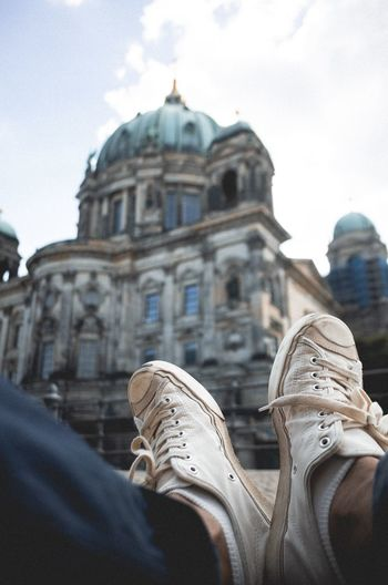 Low section of man wearing shoes against berlin cathedral