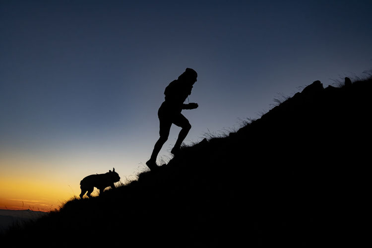 Silhouette woman with dog against sky during sunset