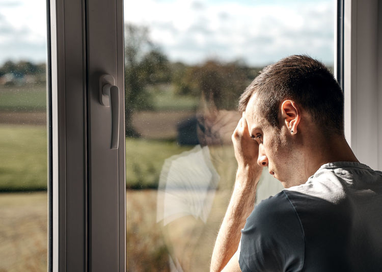 young pensive man looks out of window