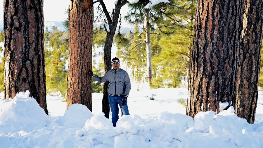 Portrait Of Man Standing On Snowy Field Amidst Trees