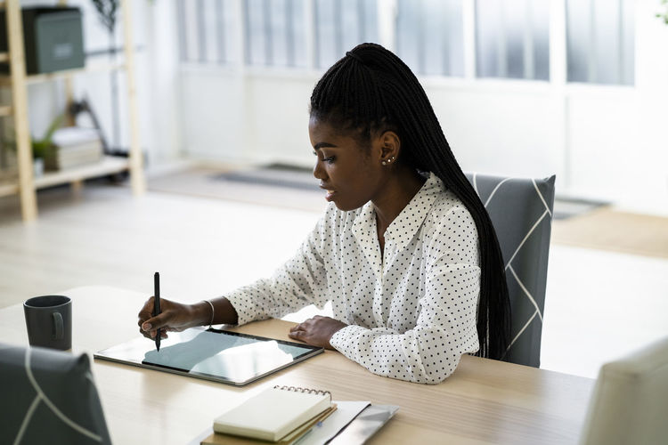 Midsection of woman using mobile phone while sitting on table