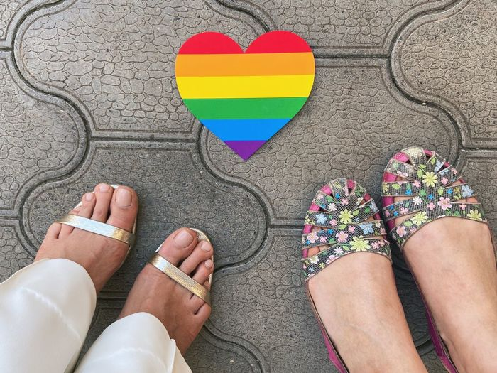 Low section of lesbian couple standing by heart shape rainbow flag
