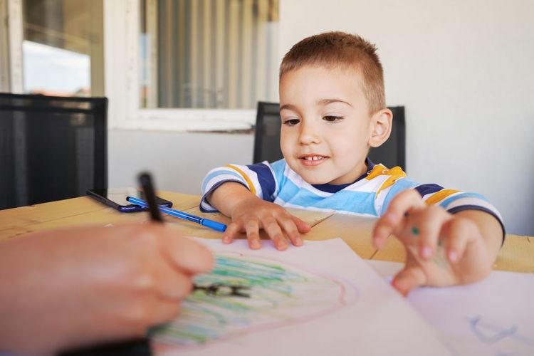 Close-up of cute boy drawing at home