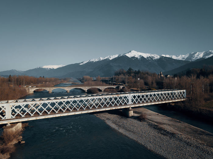 Scenic view of bridge over river against snowcapped mountains and clear sky