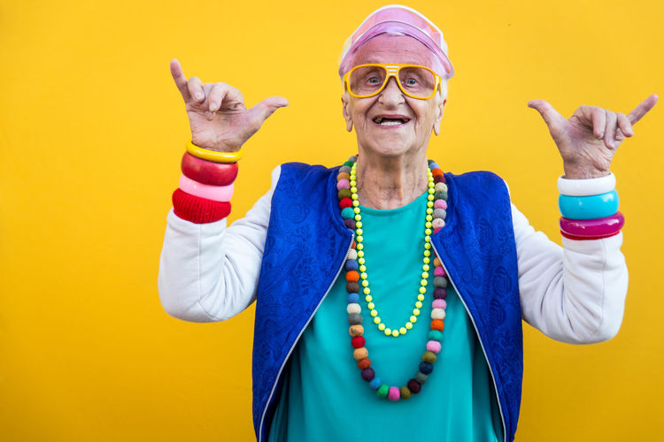 Portrait of smiling senior woman gesturing against yellow background