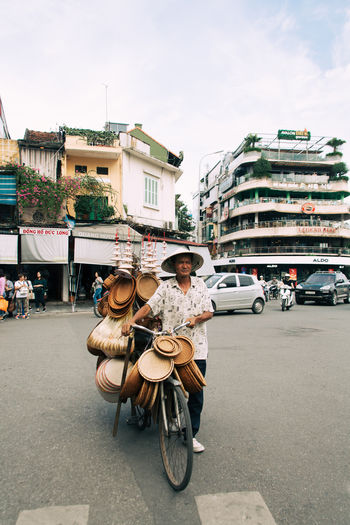 Artisan City Vietnam Architecture Bicycle Building Exterior Built Structure Car Casual Clothing City Day Full Length Incidental People Land Vehicle Leisure Activity Lifestyles Men Mode Of Transportation Outdoors People Real People Riding Road Street Transportation