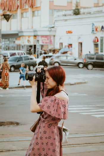 Woman photographing on street