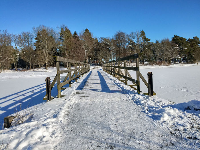 Snow covered pathway against clear blue sky