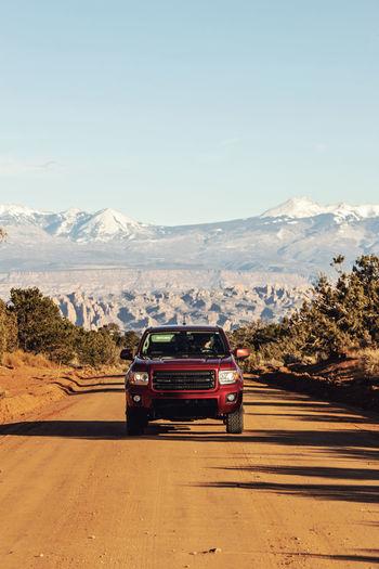 Cars on road against mountain range against sky