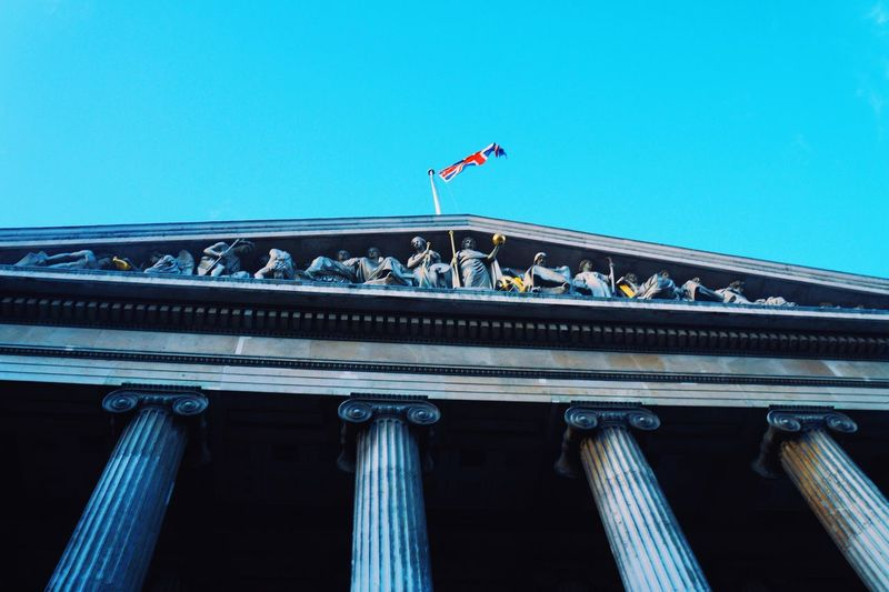 Low angle view of british museum pediment against clear blue sky