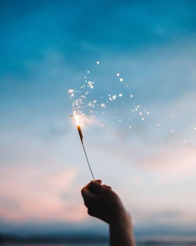 Person hand holding sparkler against sky