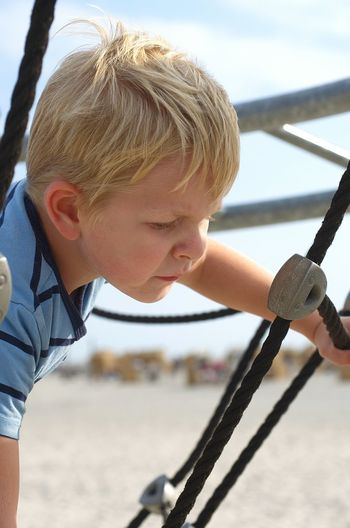 Close-Up Of Boy On Rope Play Equipment At Playground