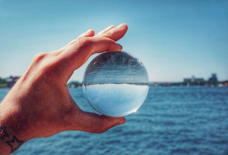Cropped image of hand holding crystal ball against sea and sky