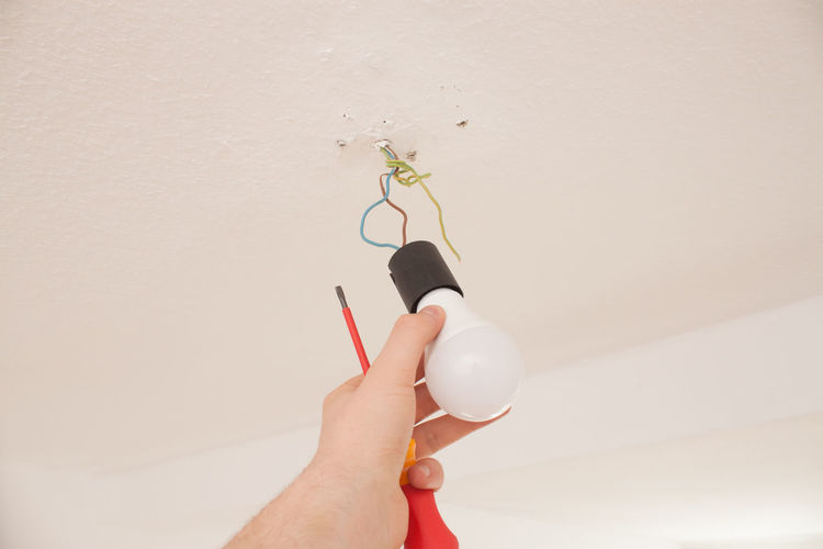 Cropped hand of man adjusting light bulb on ceiling at home