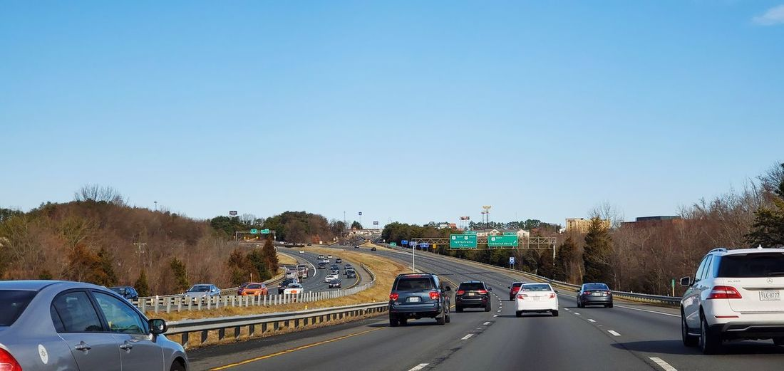 Cars on road against clear blue sky
