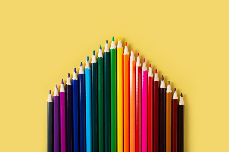 Multi colored pencils in row against yellow background