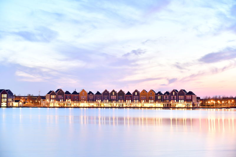 Lake by illuminated buildings against sky during sunset