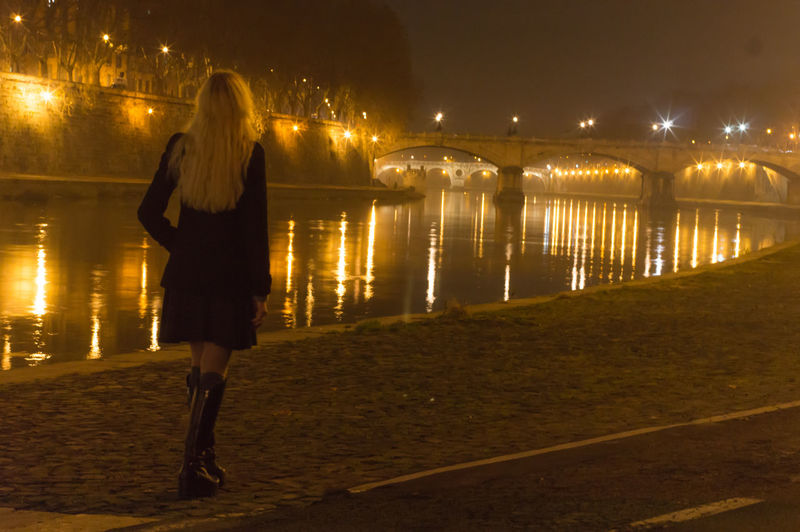 Rear view of woman walking on promenade by tiber river at night
