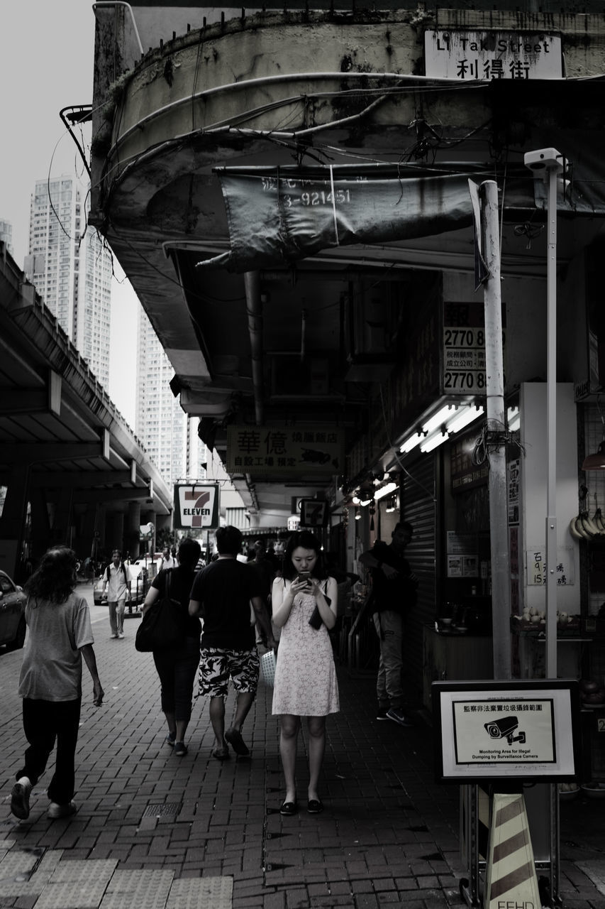 architecture, building exterior, city, built structure, women, real people, group of people, lifestyles, street, text, walking, adult, communication, men, sign, people, city life, store, script, footpath, consumerism