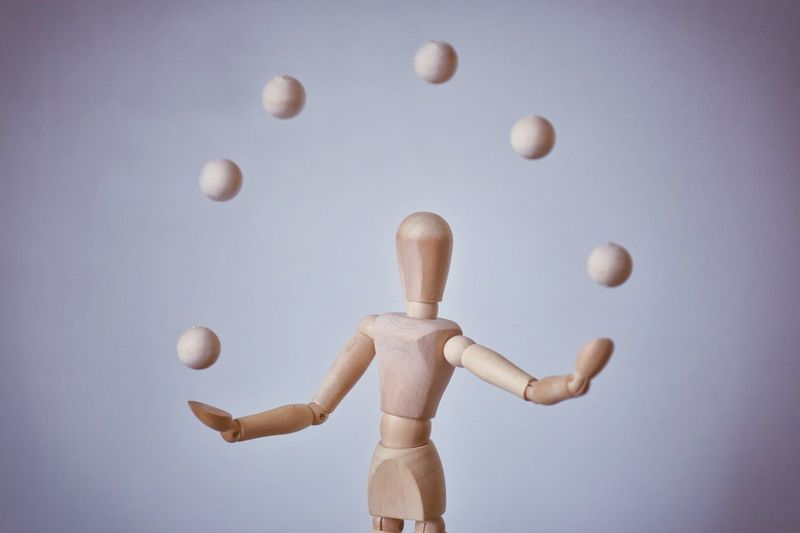 Wooden Figurine And Balls Against White Background