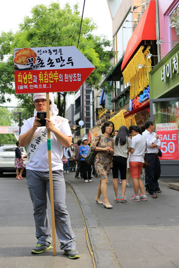 Insadong area, well known as a traditional street to both locals and foreigners Advertising Salesman Tourist Attraction Banner Building Exterior City Communication Destination Impact Information Insadong Lifestyles People Restaurant Sign Standing Street Streetfood Text Traditional Street