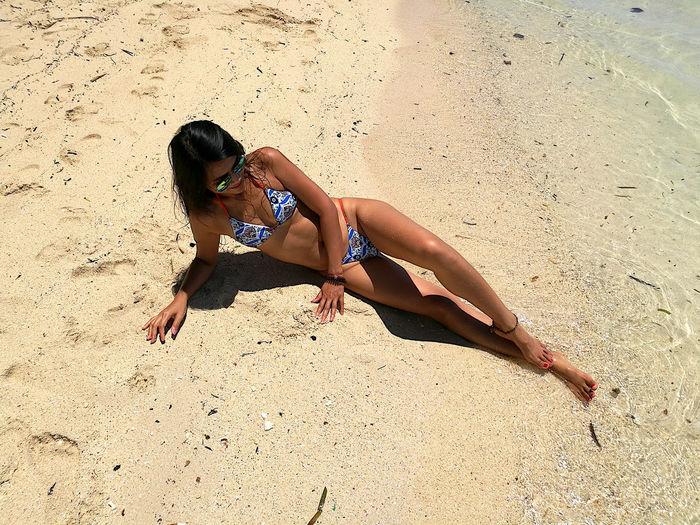 High angle view of woman wearing bikini lying at beach
