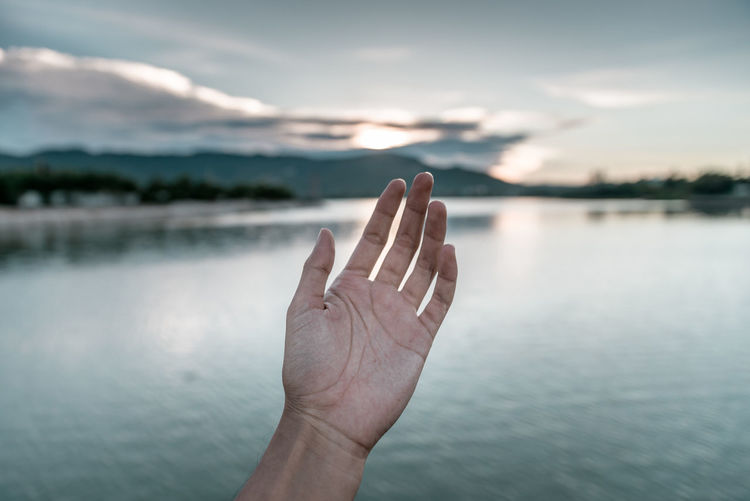 Cropped hand against lake during sunset