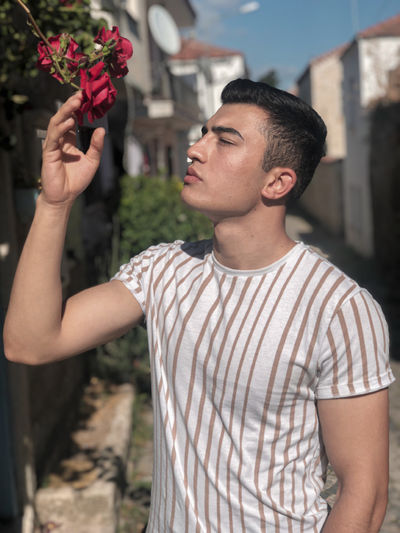 Portrait of young man holding flower