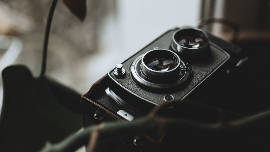 Close-up of vintage camera by window