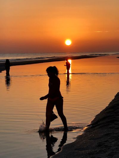 Sunset Water Sunset Sky Sea Beauty In Nature Silhouette Land Beach Orange Color Reflection Real People Leisure Activity Nature Full Length Horizon Over Water Outdoors Adult People Lifestyles Scenics - Nature